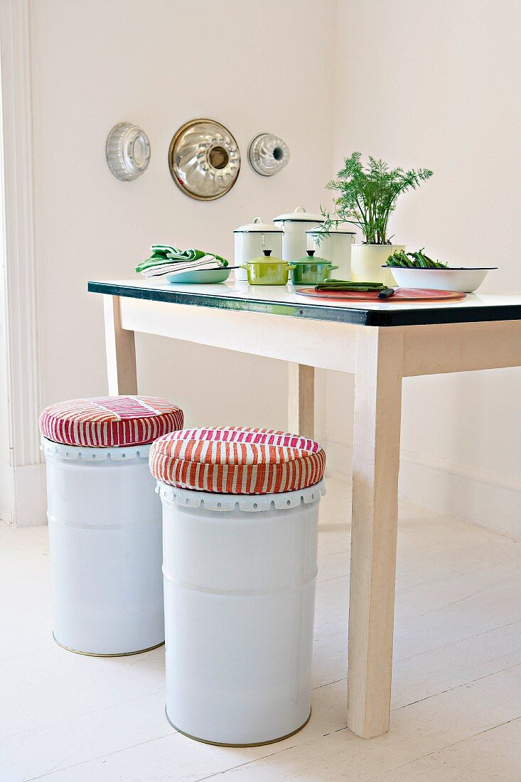 White metal stools with cushions next to kitchen table with still-life arrangement in corner of minimalist room with baking tins on wall