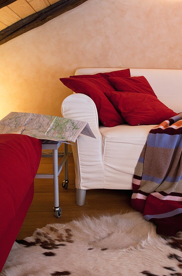 White sofa below wooden ceiling with red cushions and striped, woollen blanket; animal skin rug provides a cosy atmosphere