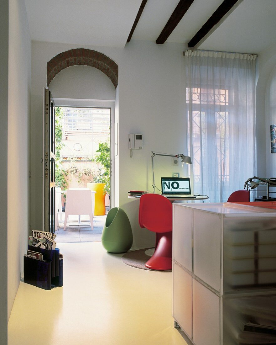 Home office with access to terrace and plastic designer furnishings in bold colours