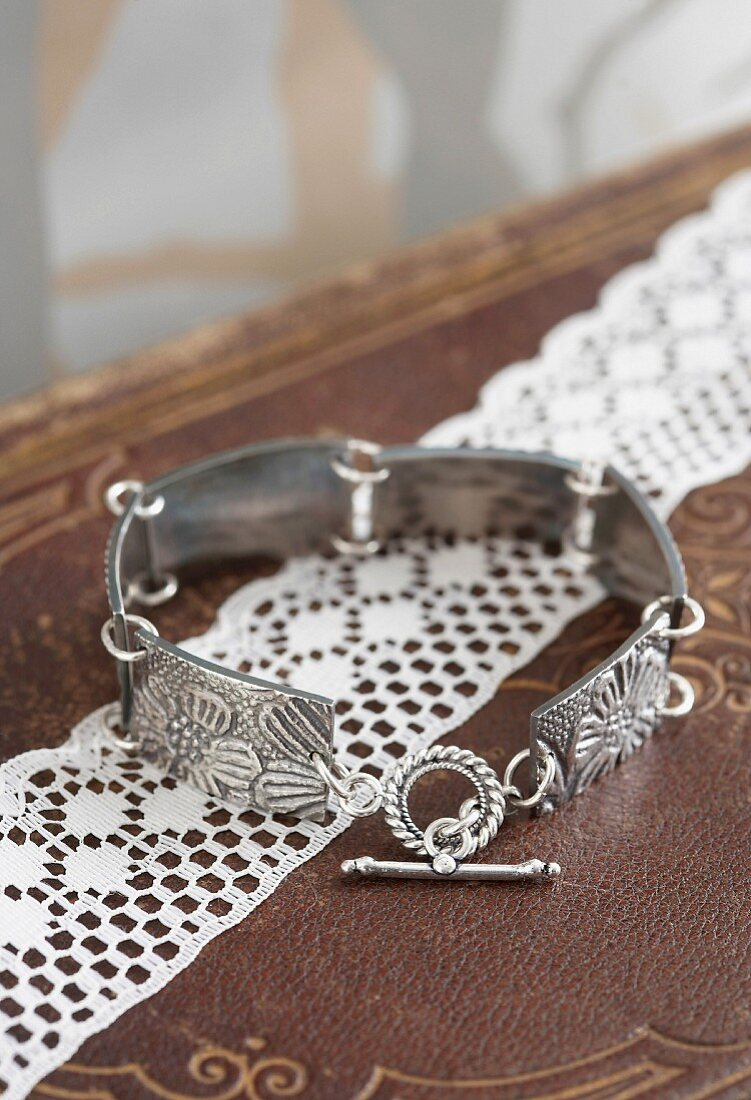 Hand made, silver link bracelet with floral pattern on lace