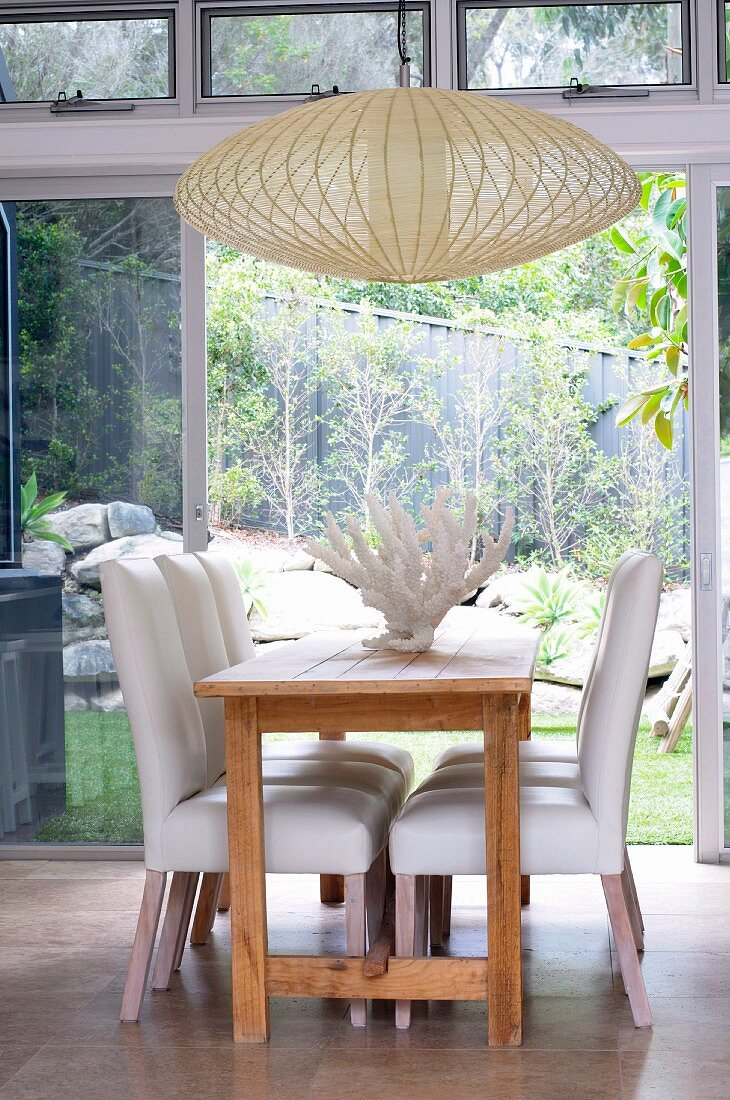 Chairs with white upholstery at wooden table and pale, basketwork pendant lamp in front of terrace doors with view of garden