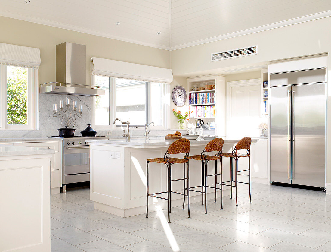 Spacious, white kitchen with long kitchen counter, stainless steel door fronts and high wicker stools at counter