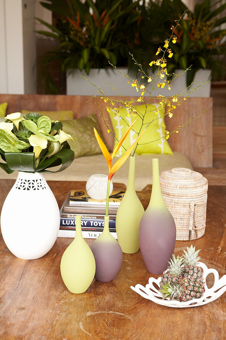 Group of vases holding single flowers and fruit bowl on wooden table