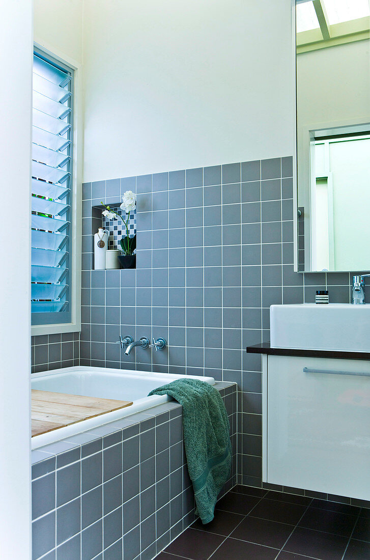 A bathroom with grey tiles, a small wall niche with a spotted pattern and a wooden, vintage-style shelf