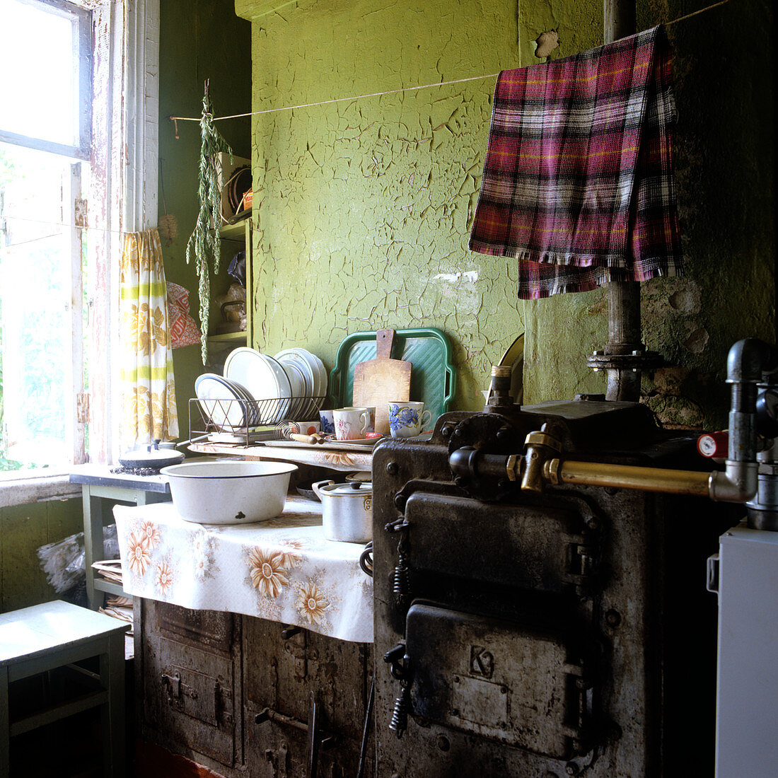 Tea towel hung above rustic, grimy stove to dry