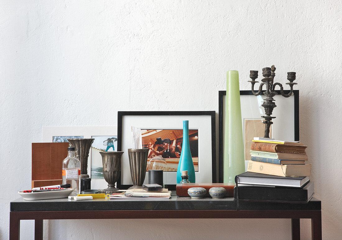 Zinnbecher, Vasen, Bücherstapel und Allerlei auf modernem Wandtisch
