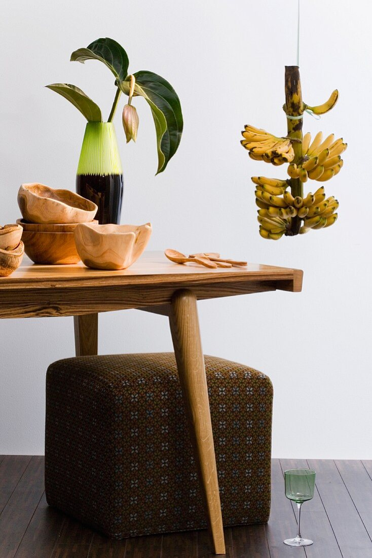 Retro-style living room (wooden table, stool, wooden bowls, banana plant)