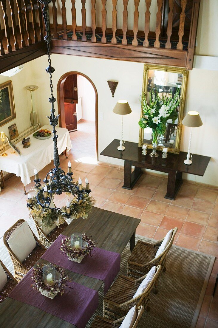 View from gallery of chandelier above dining table and wicker chairs in elegant, traditional foyer