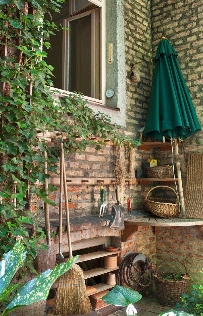 Storage rack in outside corner next to open window in brick facade