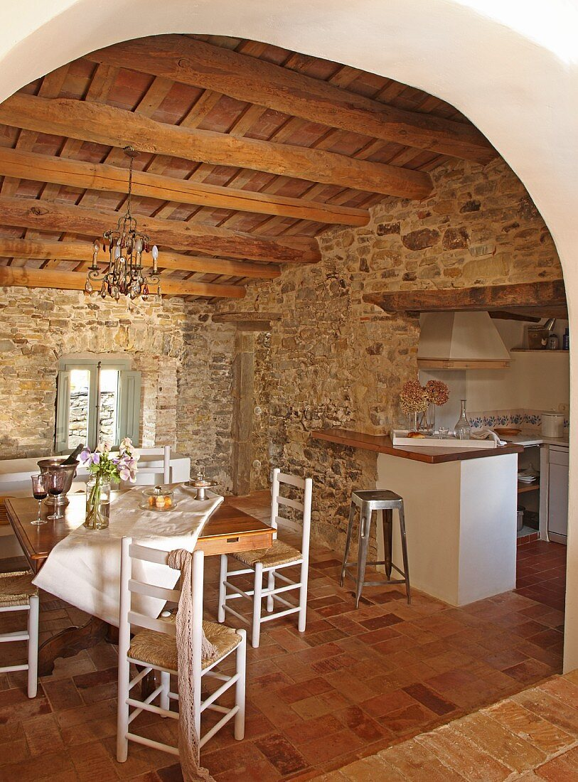 Stone walls and rustic wooden ceiling lend a Mediterranean air to a simple, white kitchen-dining room
