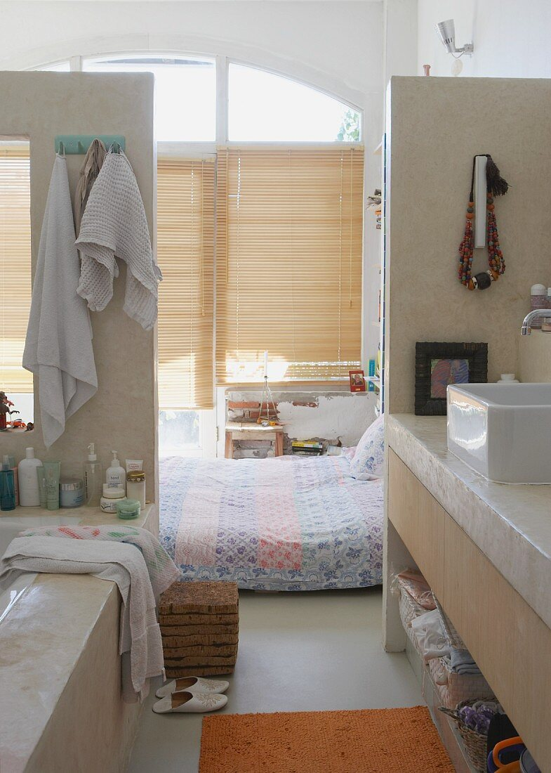 View from open-plan bathroom area - bed on floor in front of closed bamboo window blinds in loft-style interior