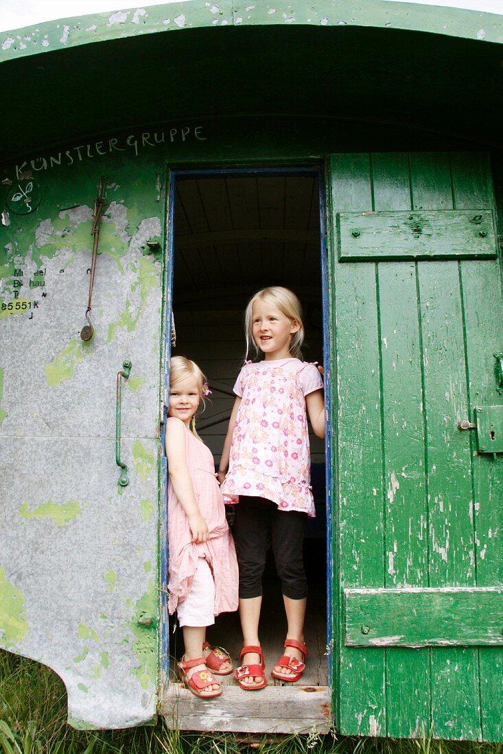 Two blonde girls in doorway of summer house
