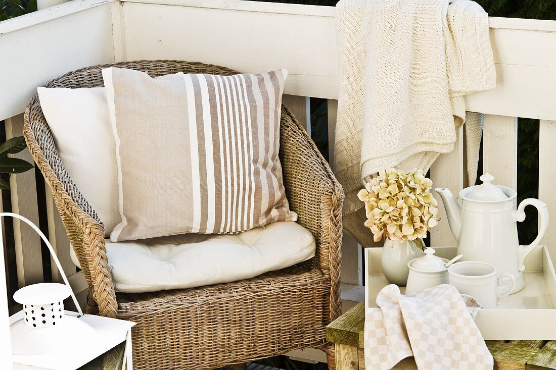 Afternoon break on veranda - wicker armchair with cushions next to tea service on side table