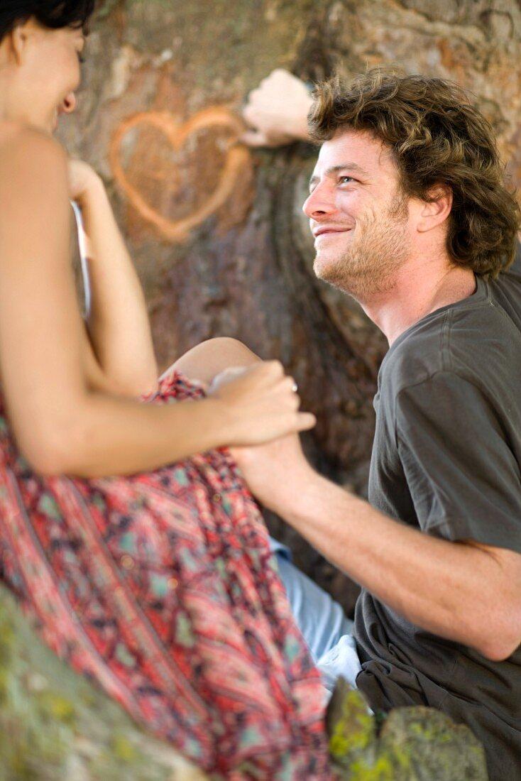 Pärchen ritzt ein Herz in einen Baumstamm