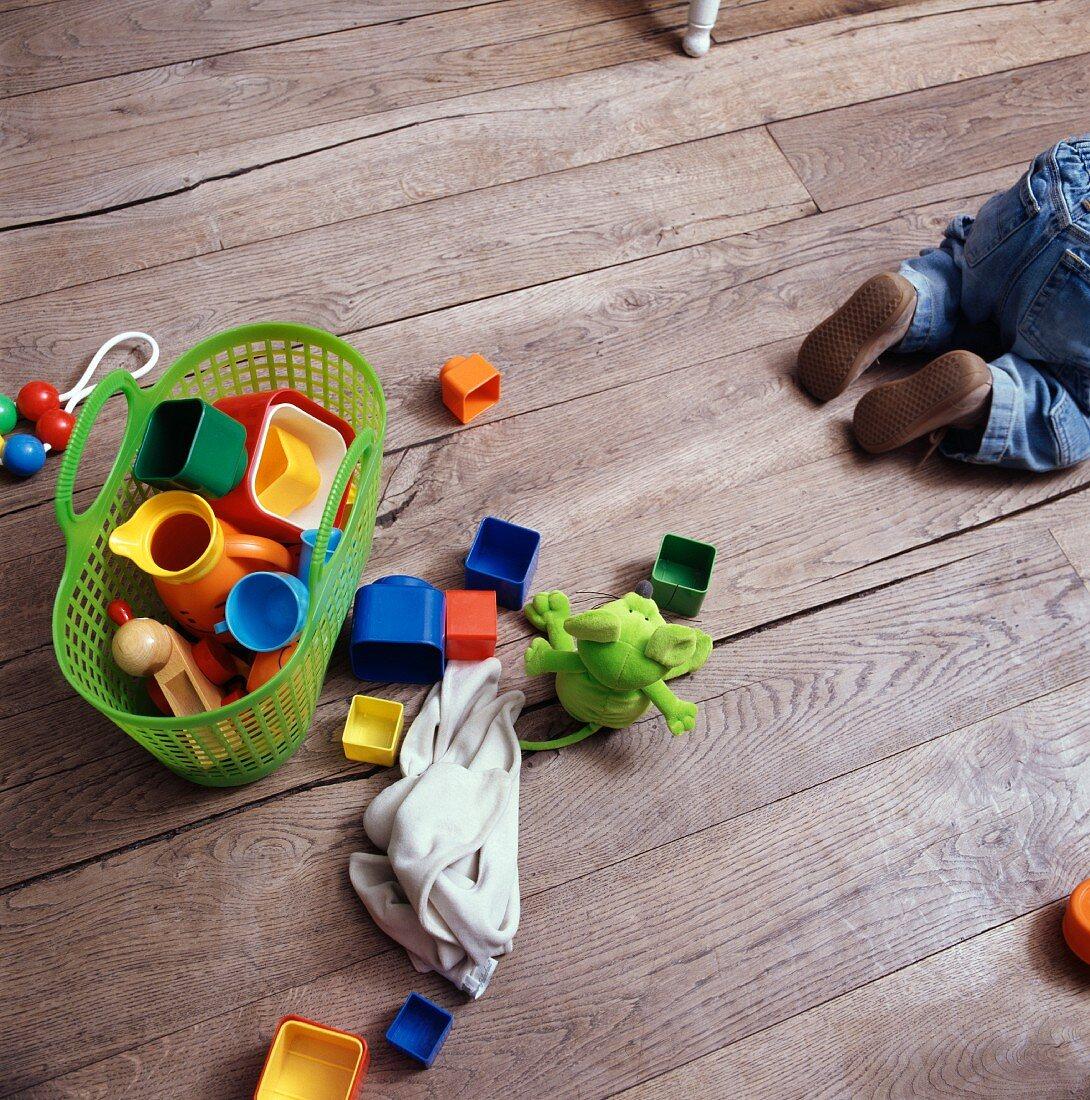 Baby und Spielzeug auf Holzboden