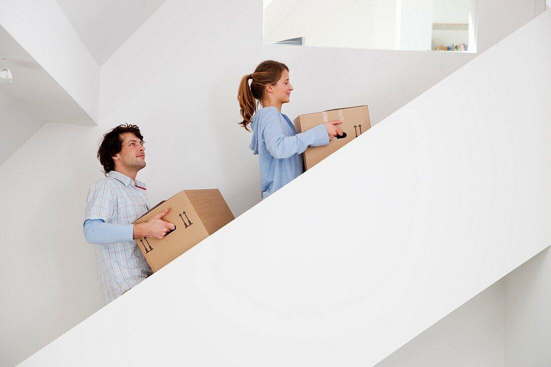 Pärchen trägt Umzugskartons über eine Treppe