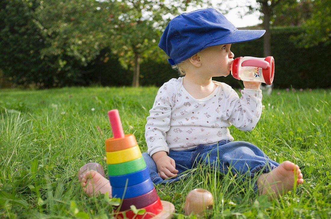 Baby drinking juice in garden