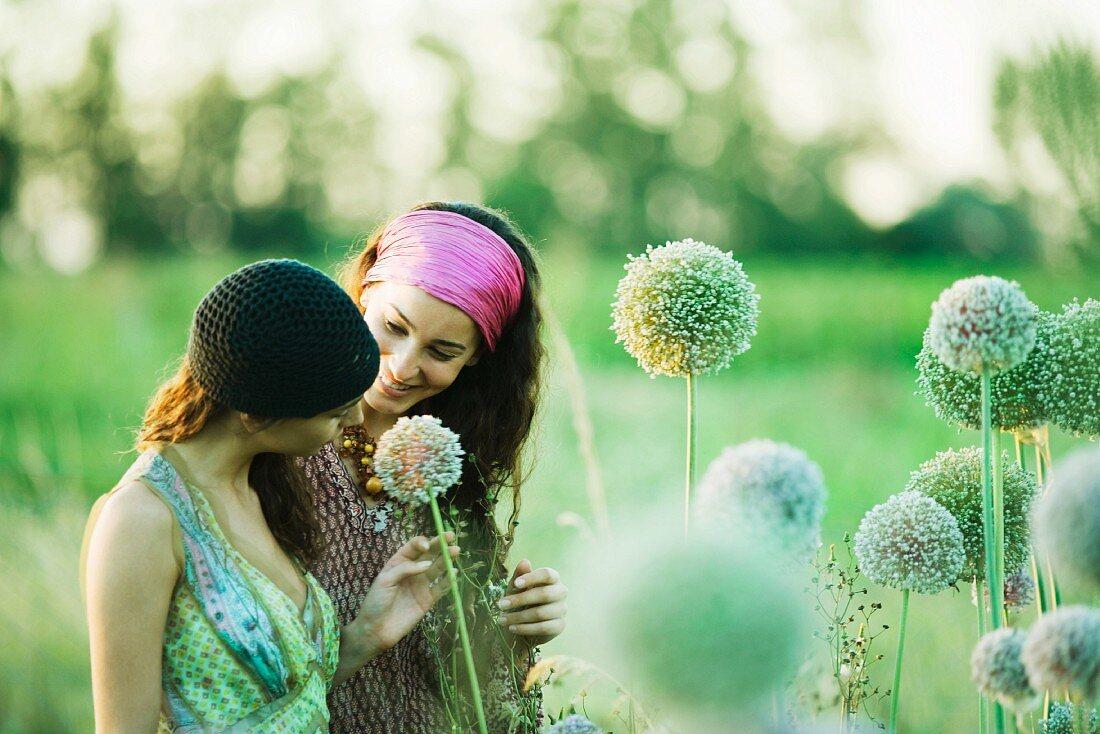 Young hippie women looking at allium flower