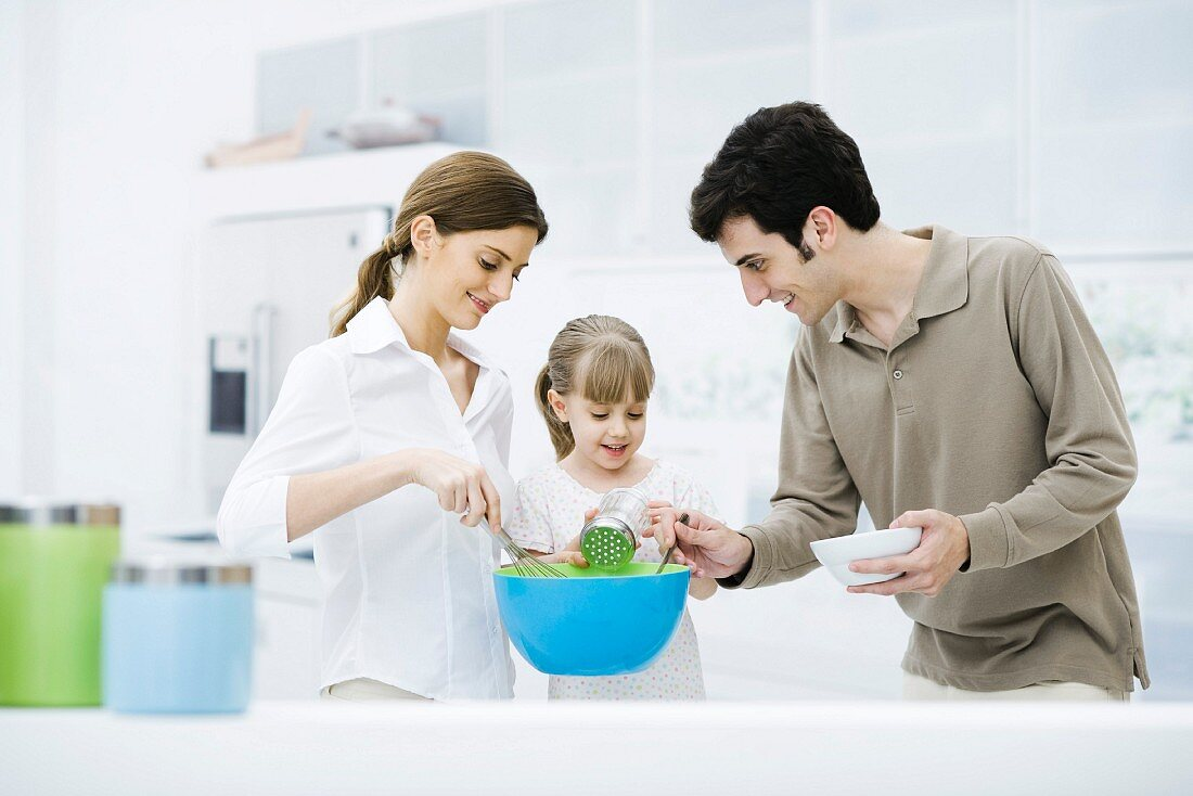 Little girl helping parents cook in kitchen