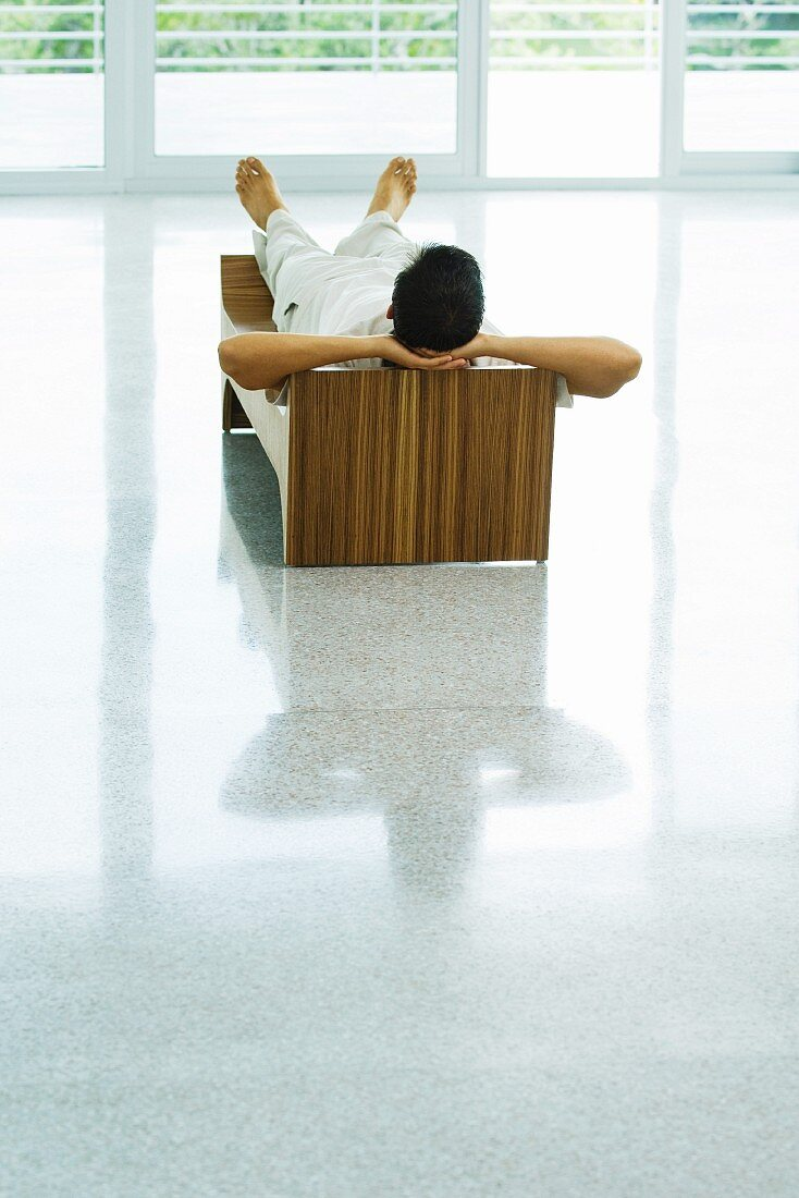 Man lying on bench, hands behind head, rear view