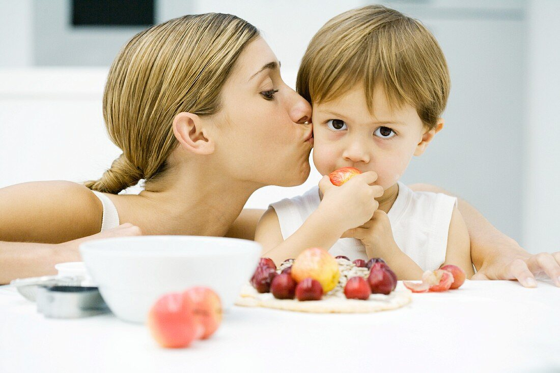Woman kissing little boy on cheek, boy eating apple