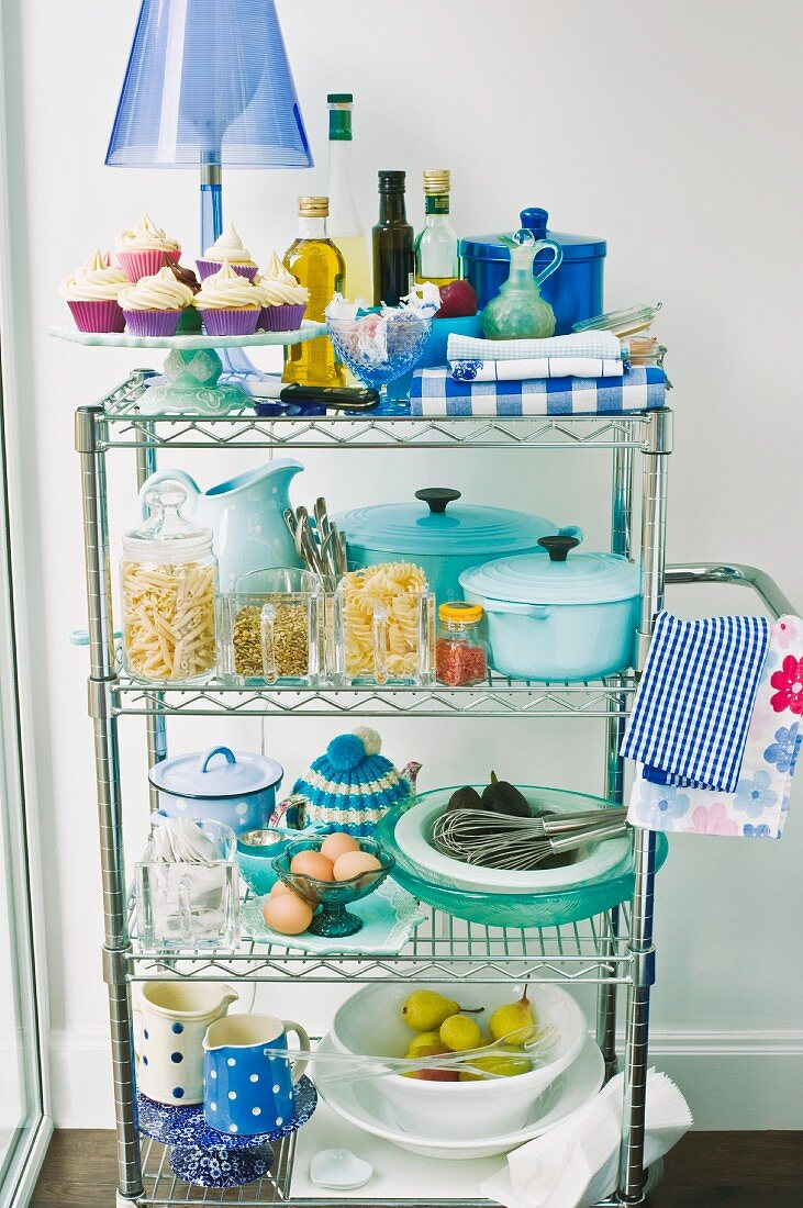 Table lamp with blue lampshade on stainless steel shelves holding kitchen utensils and storage containers