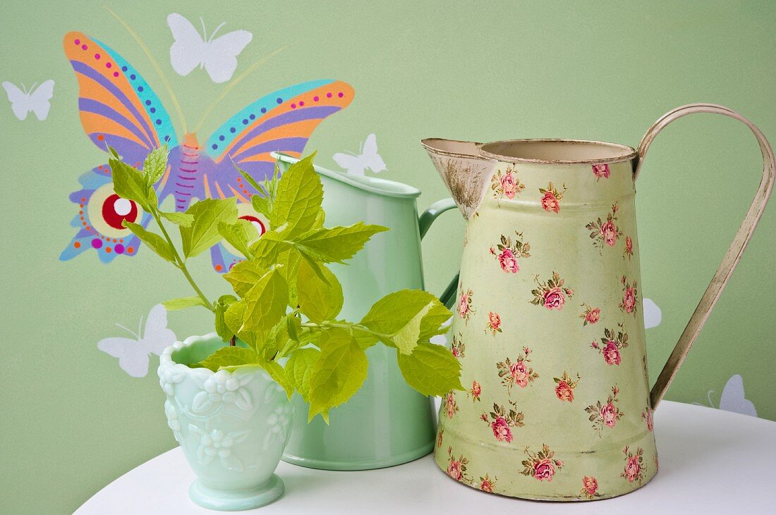 Vintage-style metal jugs against green wallpaper with butterfly motif