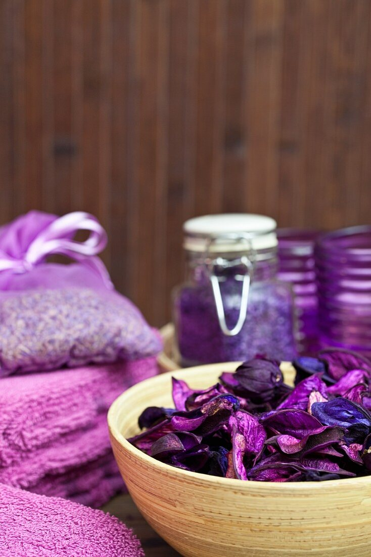 Relaxation and well-being - violet flowers in bamboo dish, bath salts and lavender bag in background