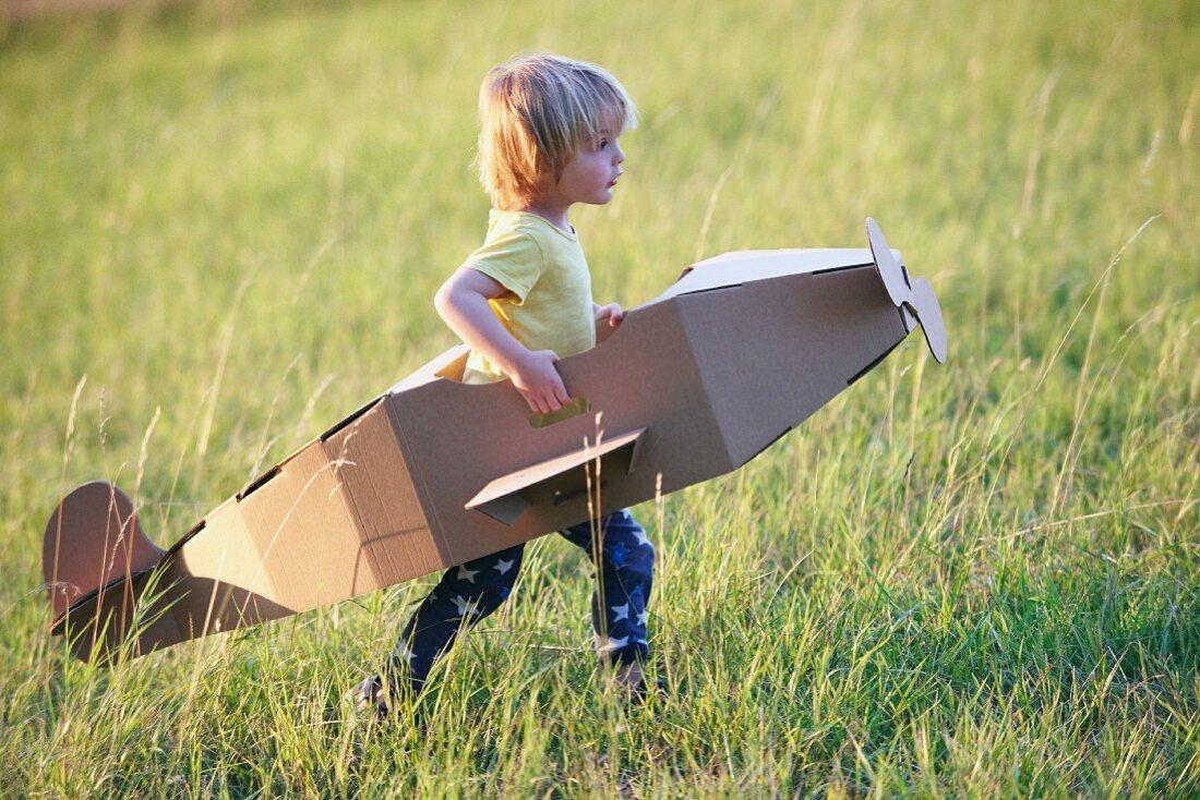 Little boy running through meadow in aeroplane made from cardboard box