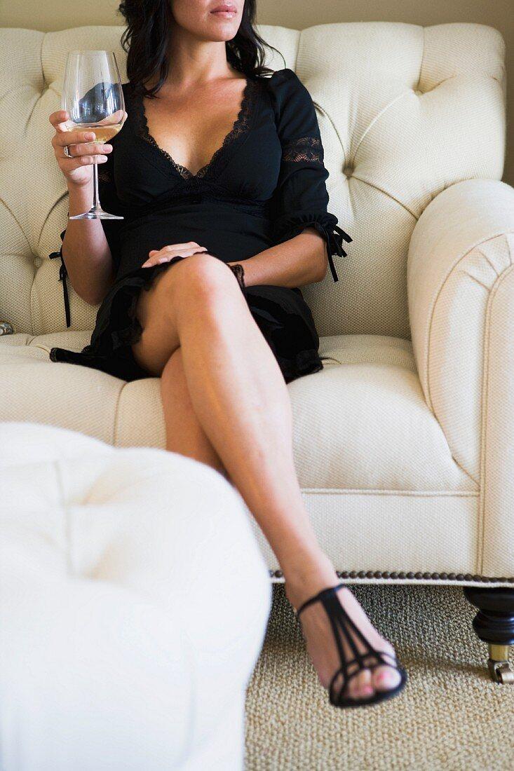 Woman enjoying a glass of wine on sofa