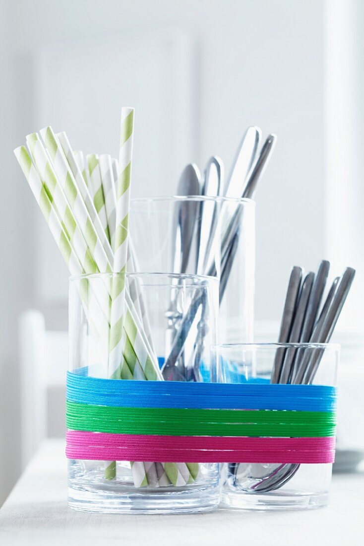 Glass containers used as cutlery holders and decorated with rubber bands