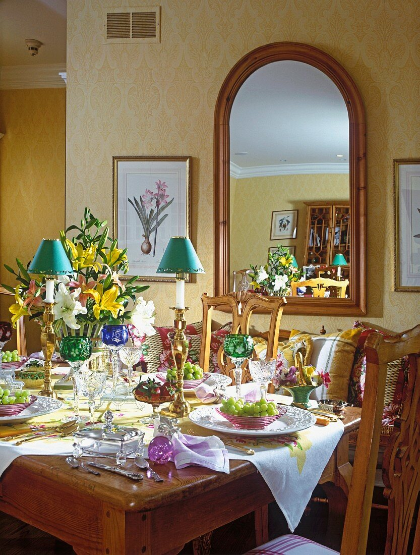 A lavishly decorated dining table with a large curved mirror in the background