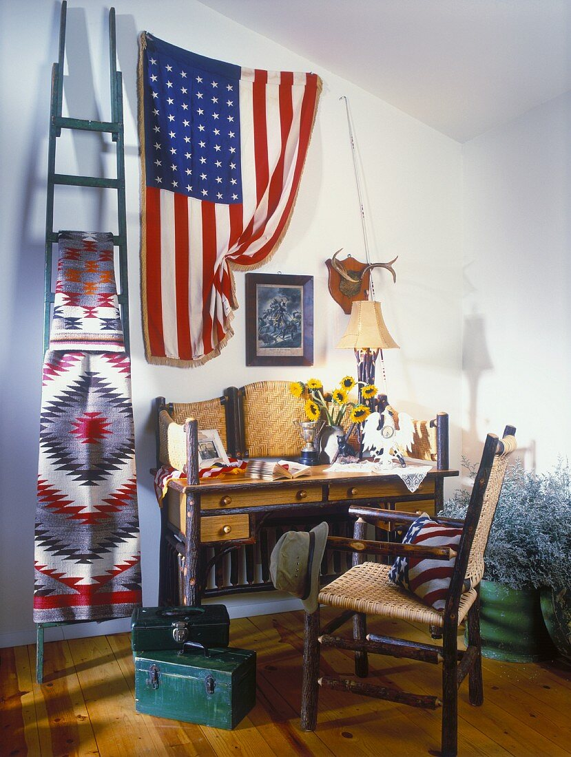 Interior with bureau, chair with woven seat and back, Native American blanket and flag of USA hanging on wall