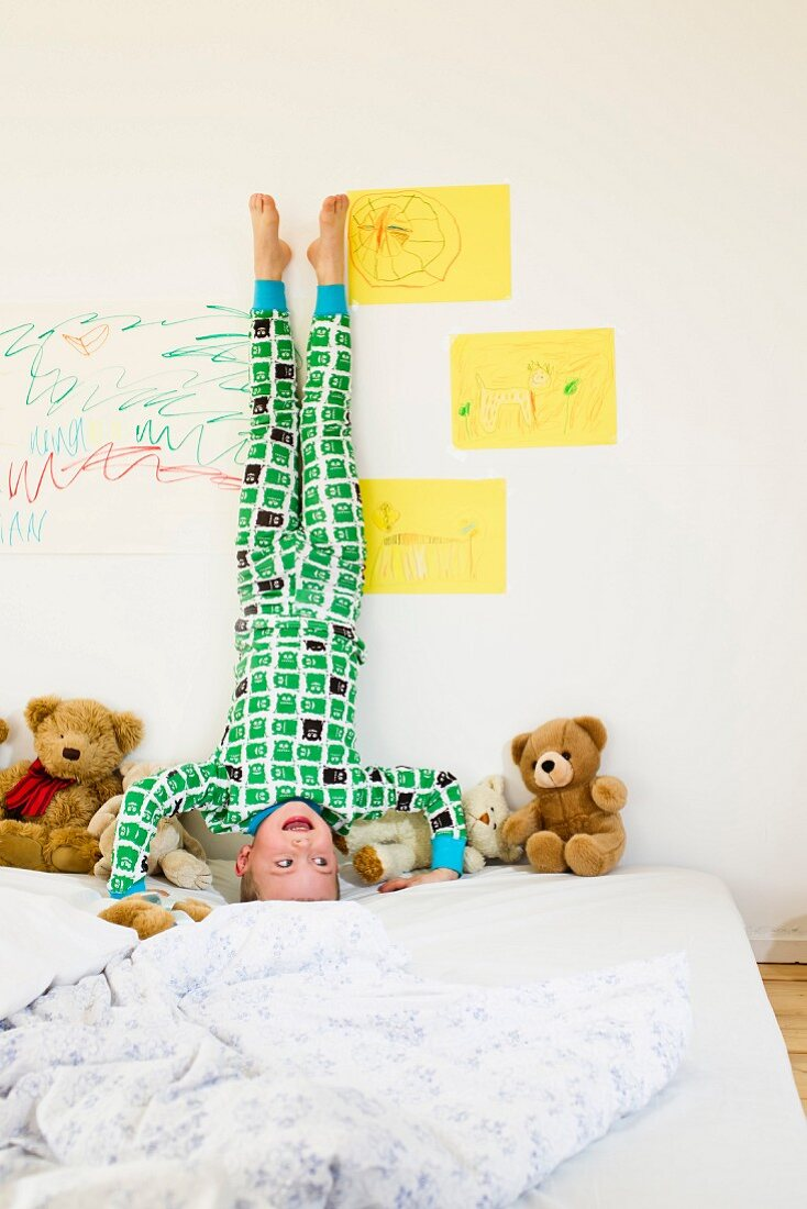 Boy doing headstand on bed