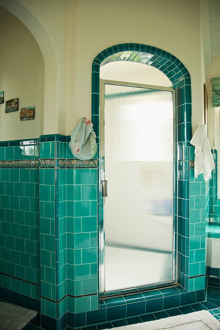 Bathroom with turquoise wall tiles and rounded archway leading to shower