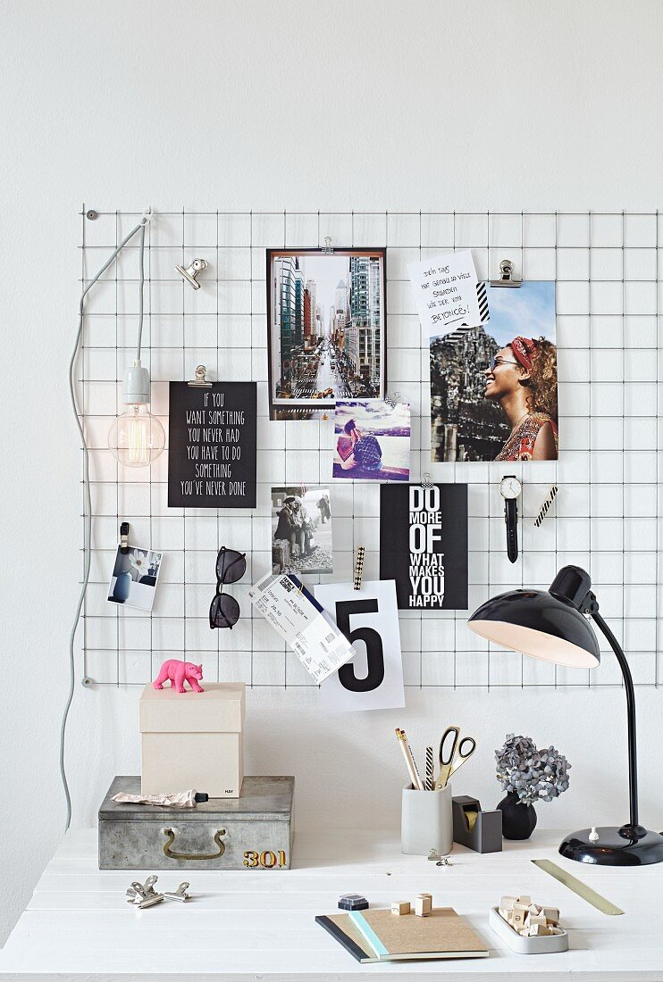 Postcards, quotes, a watch and a pair of sunglasses on a wire noticeboard above a desk