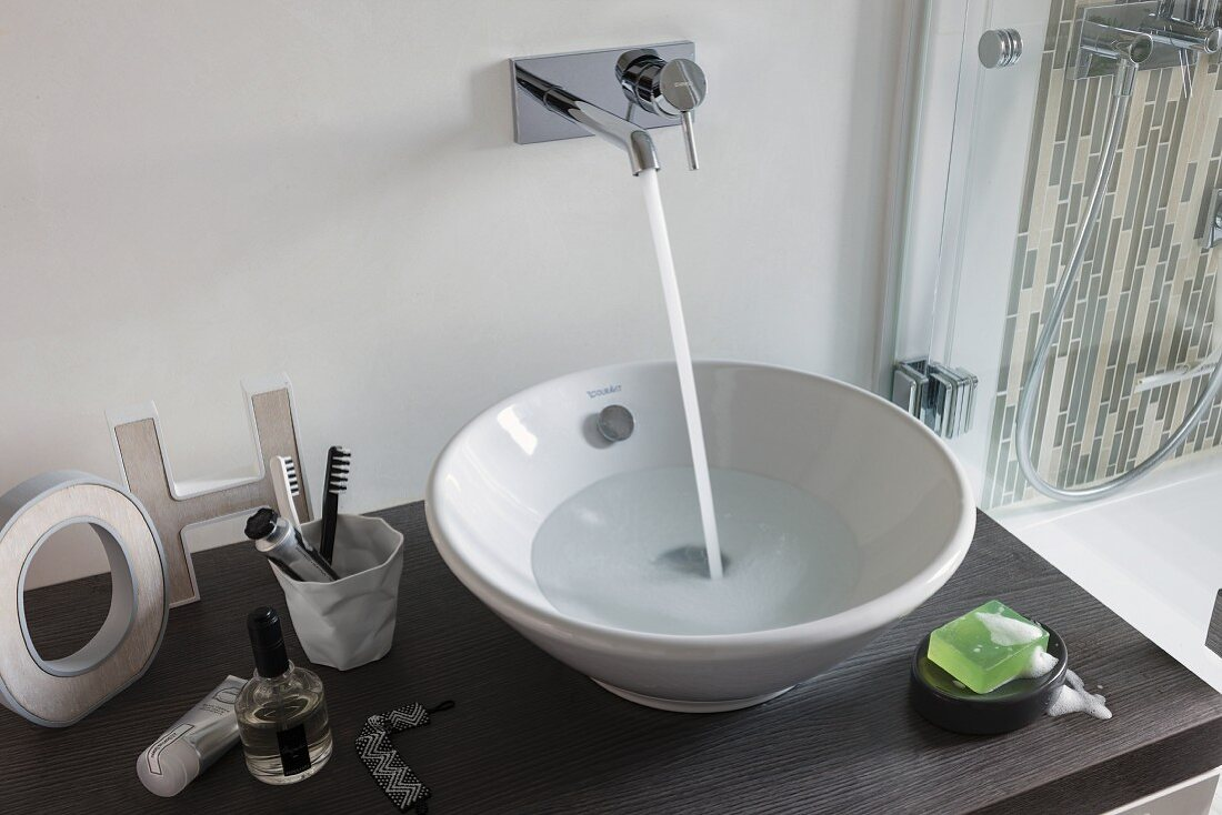 A wash stand with a bowl basin with water flowing into it from a wall mounted designer tap