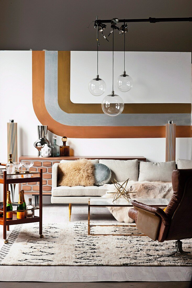 Retro living room, pendant lights with glass ball above coffee table and leather armchair, stripe decor in metal look on wall