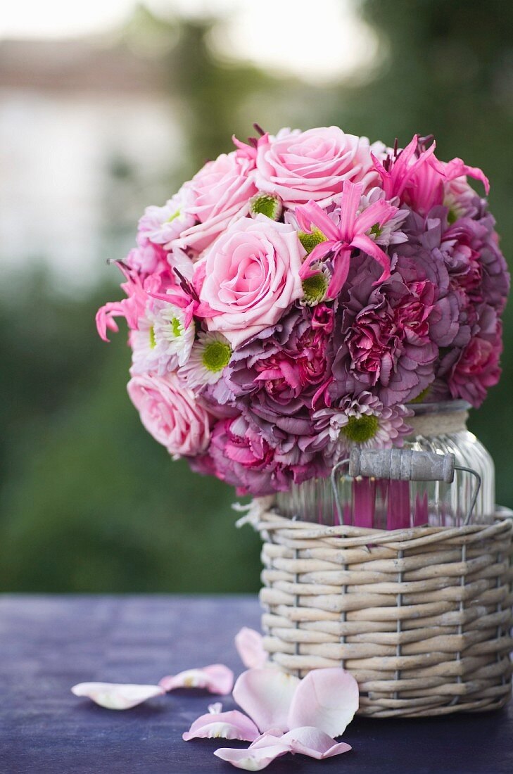 Romantic bridal bouquet of pink roses in glass vase in wicker pot