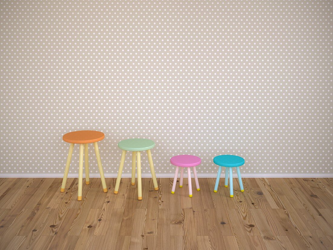 Four stools of different colours against wall with grey and white polka-dot wallpaper