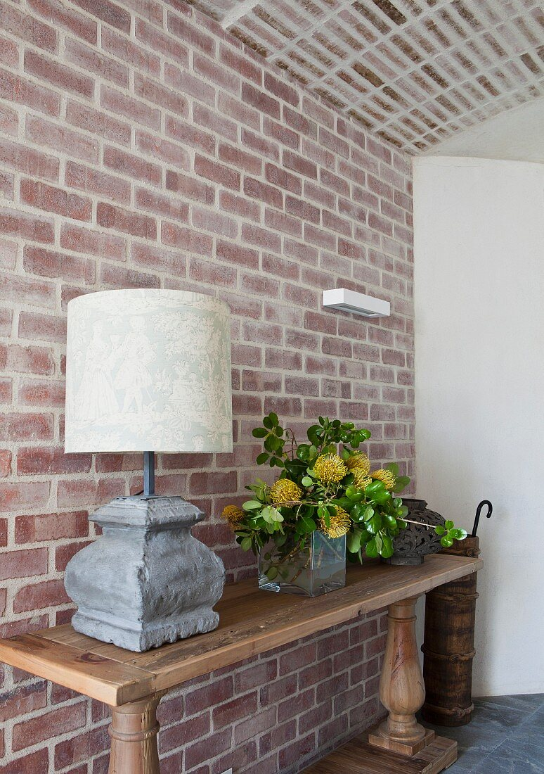Table lamp and vase of flowers on rustic console table against brick wall
