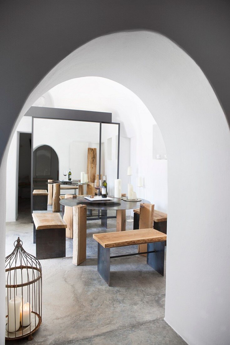 DIY stools and table on screed floor in dining area seen through arched doorway