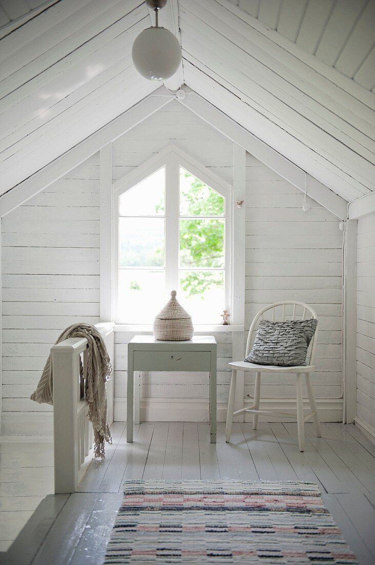 Table and chair in front of gable-end window in attic with white wooden cladding
