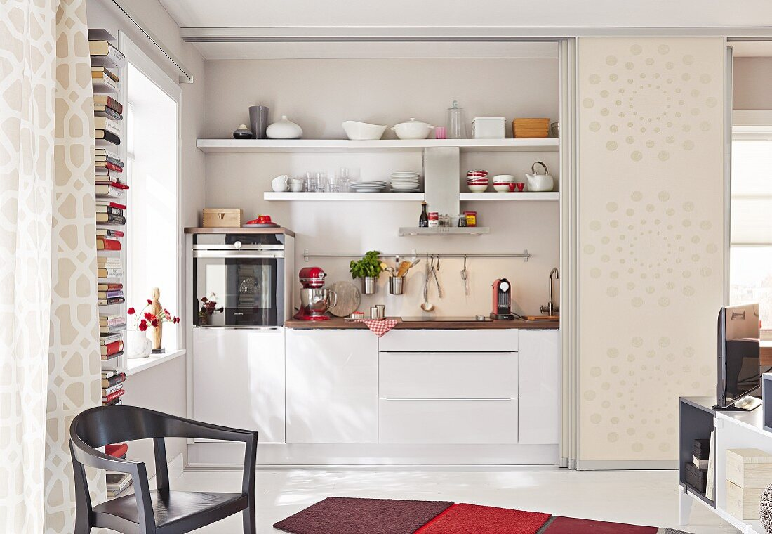 A kitchen niche behind open sliding doors in a one-room apartment