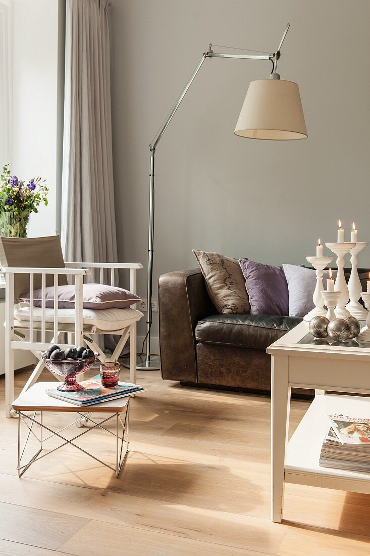 Low side table and standard lamp between armchair and leather sofa against pale grey wall