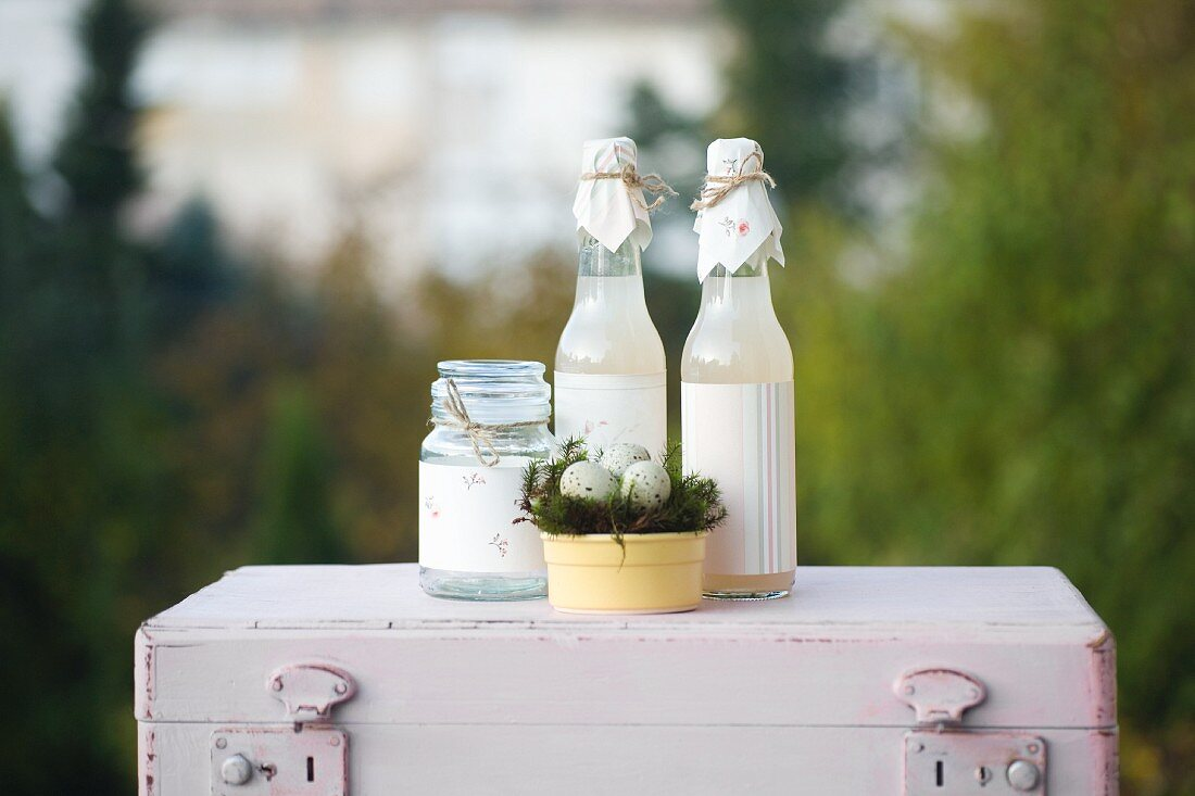Easter arrangement: jar and bottles decorated with paper and Easter nest of quails' eggs on top of pink vintage suitcase