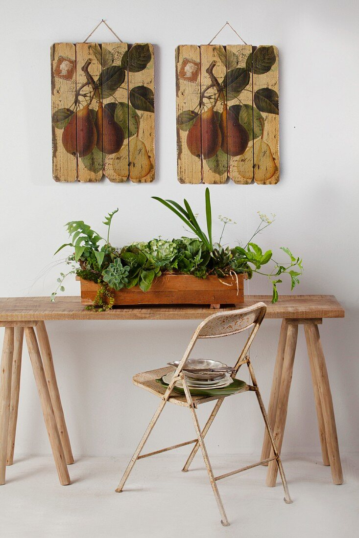 Various foliage plants in wooden window box on rustic table below wooden panels painted with botanical motifs