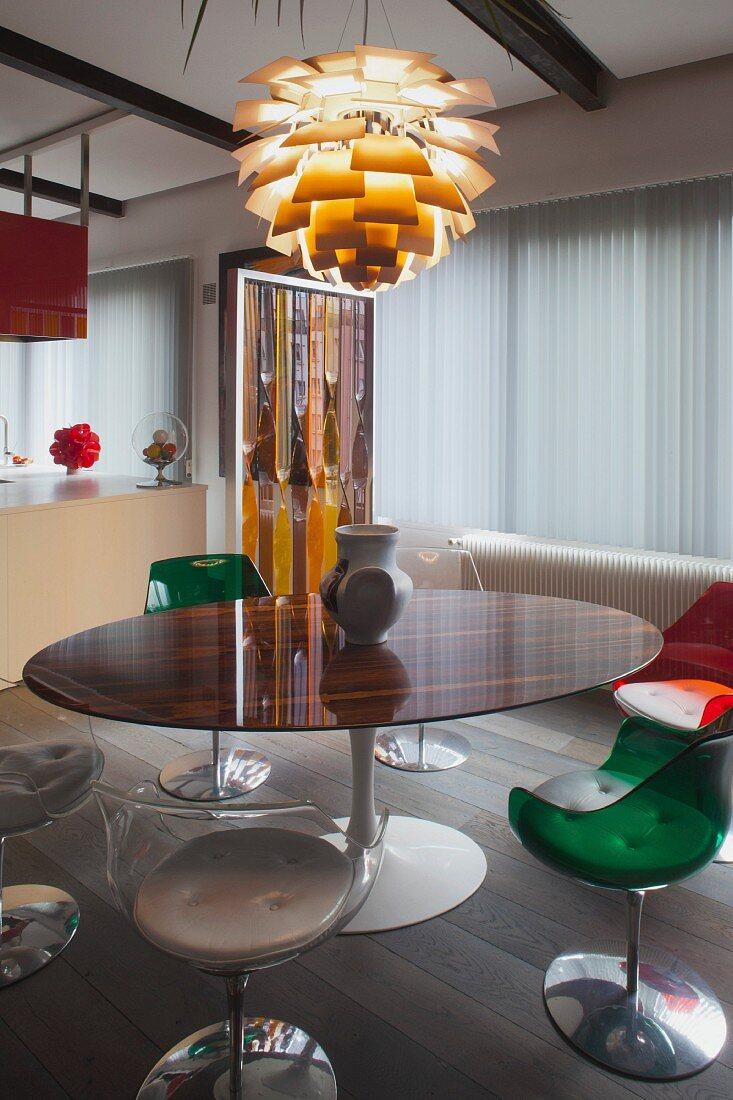 Runder Tisch und Schalenstühle aus transparentem Kunststoff, oberhalb Klassiker Artischockenlampe