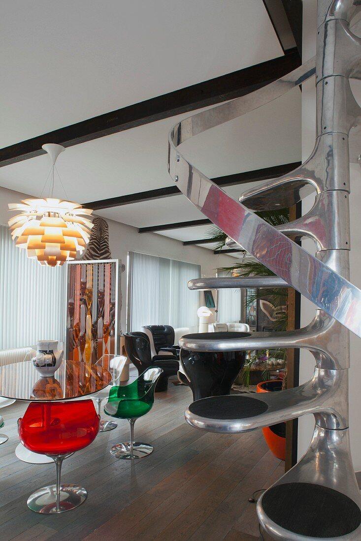 Retro Sitzplatz mit bunten Schalenstühlen aus transparentem Kunststoff unter Artischockenlampe, platzsparende Spindeltreppe