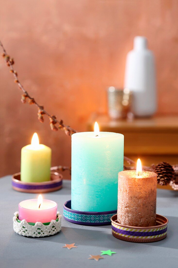 Colourful candles in saucers made from tin lids